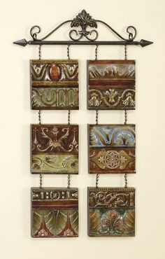This wall decor is truly a work of art that should be classified as a wall sculpture. It is created by using 6 individual tiles and hanging them from a scrolling acanthus metal bar with fleur-de-lis accents. The warm Mediterranean colors and embossd detailing are sure to add color and texture to your kitchen, bathroom, living room or home office.
