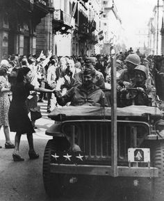 Jubiliant Romans throng the streets to greet Mark W. Clark, the conquering general, on June 5, 1944, as his driver wanders through the city in search of the Capitoline. In the rear seat behind Clark are the Fifth Army chief of staff, Major General Alfred M. Gruenther (left), and Keyes, the II Corps commander.