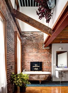 A Restored Red Hook, Brooklyn Home // Lofted ceiling bathroom with exposed brick wall.
