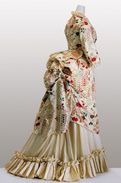 """1870's. White kimono fabric of figured """"shibori"""" silk satin; embroidery of wisteria, chrysanthemum, peony, and Chinese fan motifs in metallic threads ...This dress was remade from a Japanese kimono in London."""