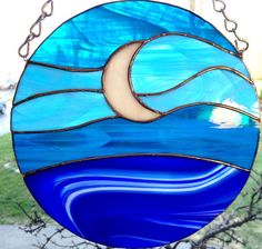 Here is a basic yet beautiful suncatcher for the water lover! This 8 diameter suncatcher has three different styles of blue glass in it that appear to change with the lighting. The moon appears to create a glow as the light fades. A great piece for the person that loves sitting by the water on a moonlit night