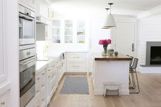 Kitchen with white walls, white cabinets, light wood floors, patterned rug, white light fixtures, white countertops, gold details, wooden tabletop, black barstools, and fireplace