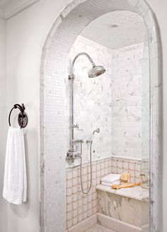 An arched entryway enhances the old-world appeal of this shower enclosure. Inside the shower, a mix of gold Calacatta marble, French limestone, and white granite tile beautifully showcase the natural patterns. #bathroomdesign #bathroomideas #bathroomremodel #walkinshowerideas #showertileideas #bhg Shower Seat, Tub Shower Combo, Shower Floor, Walk In Shower, Shower Tub, Shower Tiles, Large Shower, Glass Shower, Shower Remodel