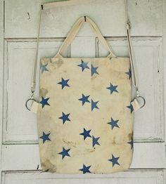 """Made from a vintage Beacon chicken feed sack from the 1940s, this foldover tote bag screams 'Murica! It has a duck canvas lining with a pocket, canvas ticking on the back, magnetic button closure and an adjustable 46"""" strap. Measurements: 14"""" x 17"""" x 2""""."""