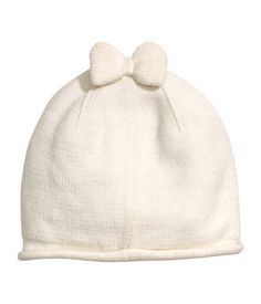 Natural white. Hat knit in a soft cotton blend with decorative bow at top and…
