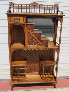 This is a gorgeous American antique Victorian etagere that is hand carved out of solid oak and dates from 1870-1880.