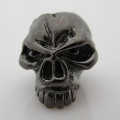 """Emerson Skull Bead in Hematite Matte Finish by Schmuckatelli Co. ~ Finish: Hematite Matte Plated,   Height: 0.52"""",   Width: 0.52"""",   Depth: 0.52"""",   Center Hole Diameter: 3/16"""",   Manufacturer: Schmuckatelli Co.,   Made in the USA,   100% Lead Free,  All measurements are approximate. A YouTube Video of this Bead is available by clicking into the photo and visiting our site at JigProShop.com"""