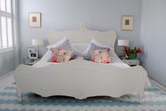 Serene room with huge white bed, aqua and white zigzag striped rug, mirrored nightstands, and soft gray walls