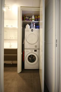 Washing machine and dryer behind closed doors in a bathroom. Wasmachine en droger netjes in kast weggewerkt