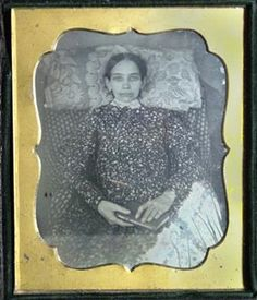 .We have learned that sometimes the eyes were painted on closed lids for post mortem photographs. She is propped up on a flower printed pillow and holds a book in her hands. The white area in the lower right of the plate is a milky area that appears to be a coating problem but adds to the strange feeling of the image.
