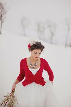 Winter wedding | Love the statement of the red cardigan with her wedding dress  #winter #weddings