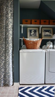 Beautiful cottage laundry room design with blue gray paint color, Sherwin Williams Storm. Stacked white laundry room shelves with corbels filled with woven baskets and blue beach art: blue seahorse and crab prints over side-by-side white washer and dryer accented with white and blue chevron rug.