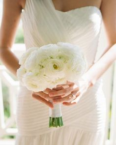 The bride carried a simple bouquet of only white ranunculus.