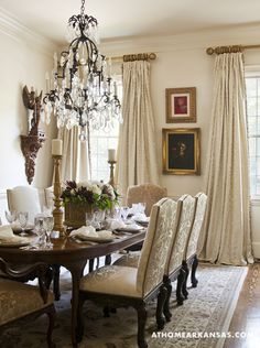 European antiques, contemporary art and a mix of iron and gilded patinas mingle in the dining room. The luxe Scalamandre silk on the custom window panels is tempered by an understated, cream-on-cream palette.