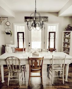 A gorgeous rustic inspired farmhouse kitchen with a vintage feel. Love the mixed matched dining chairs and that hanging grocery scale clock by Mismatched Dining Chairs, Dining Room Chairs, Shabby Chic Dining Chairs, Cottages And Bungalows, Shabby Chic Kitchen, Farm Kitchen Decor, Vintage Home Decor, Cheap Home Decor, Living Room Decor