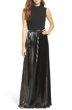 Modern, minimalist and striking with a sleek mock-neck top and knife-pleated metallic skirt.