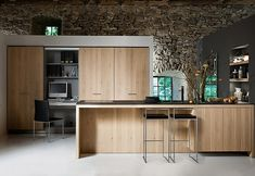 Kitchen minimalism again.  No handles.  Height.   Stone.  And fabulous stools.