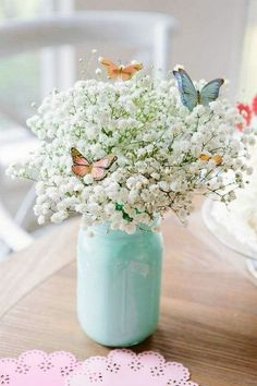 mason jar, painted in light blue, filled with white flowers, small butterfly decorations, floral centerpieces theme ▷ 1001 + ideas for flower arrangements to decorate your home this spring Butterfly 1st Birthday, Butterfly Birthday Party, Butterfly Baby Shower, Garden Birthday, Spring Birthday Party Ideas, Spring Party Themes, Butterfly Garden Party, Flowers For Birthday, Baby Girl Birthday Theme