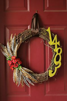 address number fall wreath. Like the feathers crossing but not thrilled w fake flower choice