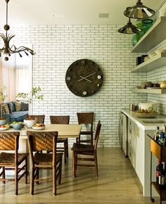 """""""My client liked the patina and character of an old farmhouse but wanted to keep the home very modern,"""" says Gambrel. """"I found that juxtaposition to be unexpected."""" The result: subtly timeworn materials, such as rustic tiles and bleached-oak floors. """"From a functional perspective, I like having my dishes exposed and on shelves so I can access them easily,"""" he says. """"I think all of your kitchen tools should be selected for both functionality and aesthetics, such as Staub cookware."""""""