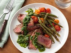 Stretch your strip steaks by serving smaller portions alongside a hearty serving of grilled green beans and tomatoes.