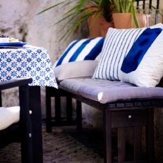An outdoor bench with lots of cushions in white and blue.