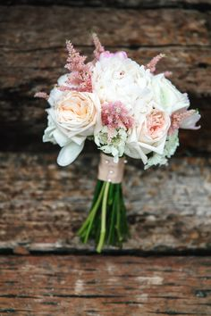 The bride carried a bouquet of peach and blush garden roses, white pincushions, white peonies, and pink astilbe. |   Photo by Barbara B Covington Photography
