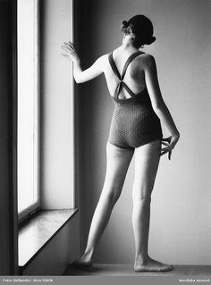 Modebild. Modell i stickad baddräkt poserar i ateljen i ljuset från ett fönster. Fotograf: Sten Didrik Bellander, 1950