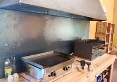Zona de cocina, con barbacoa de carbón y plancha de gas, para cocinar en verano cómodamente al aire libre
