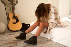 low bed, wood floors and guitar