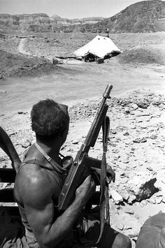 An Israeli soldier patrolling the border between the Negev Desert and Jordan, photographed by David Seymour of Magnum (1952). Note that he is carrying an uncocked M1928A1 Thompson submachine gun, and that the Cutts compensator fitted onto the end of the barrel has rotated such that the sight blade points down, which would cause the gun to rise when fired by diverting propellant gas downward, especially in the fully-automatic mode.