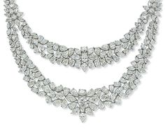 "A DIAMOND NECKLACE, BY NSOULI. The necklace designed as a double-swag of graduated pear, marquise and oval-shaped diamonds, each mounted with a central diamond cluster of floral motif, gathered by similarly set diamond terminals to the double-row vari-cut diamond neckchain, weighing a total of 83.91 carats, 33.0cm long, stamped ""750"" Signed Nsouli"