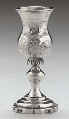 JUDAICA:- A 19TH CENTURY RUSSIAN PROVINCIAL (LITHUANIAN) KIDDUSH CUP,  MARK OF MG (Cyrillics), VILNIUS, 1862,  Thistle-shaped bowl engraved with foliage on a stippled ground, resting on a leaf calyx above a baluster stem on stepped, shaped circular foot, 4¼ in. high (11.1 cm.), 2.5 oz.