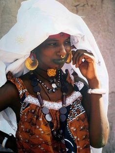 Africa | This young Fulani woman is making a deliberate show of her wealth at the weekly market in Jenné. Her nose ring, earings and neck pendant are gold, her bracelets silver and her necklace made of European glass beads. Many wealthy women of Jenné are financially independent of men; they inherit gold jewellery, and every woman has her own herd. Mali | ©Angela Fisher, Africa Adorned, 1984