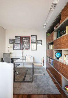 A estante, que abriga todos os livros, foi desenhada especialmente para o escritório. As cadeiras (São Romão Móveis), os quadros (Urban Arts) e o tapete complementam a decoração.