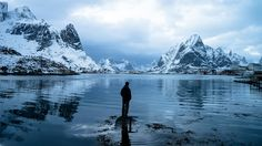 A man looks across the bay at the dynamic city of Reine in Norway.