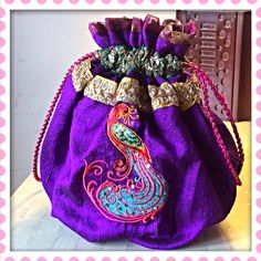 Beautiful peacock motif embroidered onto the purple rawsilk potli to add to its allure ! Made for very special occasions.