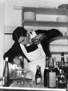Alain Delon expertly mixing punch, 1960