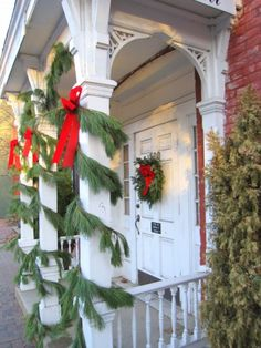 "Love this evergreen wrapped porch. Use our 20"", 28"" or 32"" mixed wreath with our 25' garlands to create a similar look. Top off with traditional red bows."