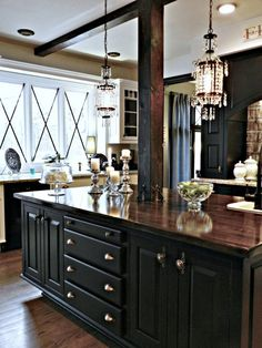 kitchen island with mahogany stained top and black cabinets