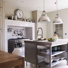 white subway tile fireplace hearth with modern stainless steel stove, built in cabinets, kitchen island, UK