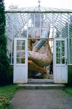 In the Greenhouse: A Towering Figure Enclosed Within a Glass Greenhouse by Susanne Ussing