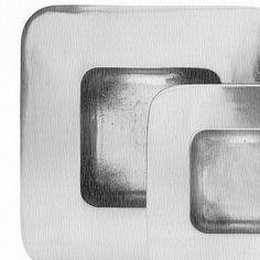 Set di 2 ciotole carré in alluminio con  angoli smussati e larga ala esterna. Lo spessore delle due ciotole è di 3 mm sia per l'ala che per la parte concava.  La lavorazione e' artigianale con fusione in terra francese. Design di STRA-DE STRATEGIC-DESIGN.