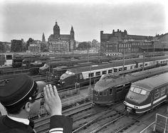 Een conducteur van de NS kijkt uit over de ...1964 Centraal Station Amsterdam