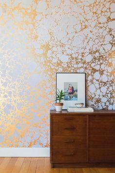 Também no estilo obra de arte, esta parede parece 'manchada' por tons dourados, o que deixa o ambiente mais despojado