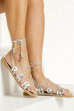 Our signature Danae gladiators are inspired from the ancient Greek wave motif as it also appears in our logo. This pair is made from silver leather with adjustable white slim ties that can be worn high up or low at your ankles, detailed with silver plated beads and coins. Top quality lace up sandals with anti-slip rubber sole for optimum comfort suitable for everyday wear from day to night. Available in 5 colors (black, tan, gold, silver and white) with silver or 24k gold plated…