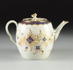 """A WORCESTER PARCEL GILT TEAPOT, : Lot 0568  A WORCESTER PARCEL GILT TEAPOT, the lid with high relief rose finial and decorated with blue band to rim beneath parcel gilt scrolls and foliate garlands, centering a white ground with blue and parcel gilt floral sprays, the body decorated with blue glaze band to shoulder beneath parcel gilt scrolls and foliate garlands, the body decorated with blue underglazed and parcel gilt floral sprays. Height: 6"""""""