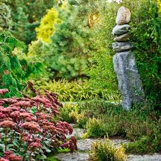 A stone cairn balances beside Sedum 'Matrona' and teucrium, which muscle out any weeds in the cracks between the stones of the pathway of this stunning late-season garden. | Photo: Jim Westphalen