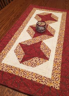 Winter berries and golden stars shine on this table runner. What a beautiful addition to your holiday table!  Three star blocks are set on a cream textured fabric. The red berry and gold berry fabrics are used in the borders. The backing is the same red berry fabric making this table runner truly reversible.  The runner measures 32 x 16 1/2 inches. The fabrics are high quality cottons. The batting is a dense cotton. The quilting is a mix of vine, cable and top stitching It is finished wi...