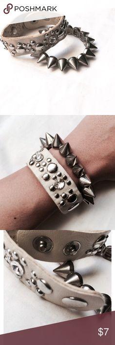 Leather Wrap & Spike Bracelet Set Gently used bracelet set. Off white wrap bracelet w/ adjustability. Has silver studs & jeweled embellishments. Elastic, plastic spiked bracelet w/ silver finish. Looks great together or separate! Jewelry Bracelets
